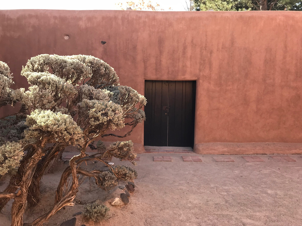 The interior wall of a patio at Georgia O'Keeffe's Abiquiu garden. It was this door in the wall that captured her imagination, inspiring her to want to own the property and garden. Photo by Jennifer Jewell, used with permission of The Georgia O'Keeffe Museum, 2017. All Rights reserved.