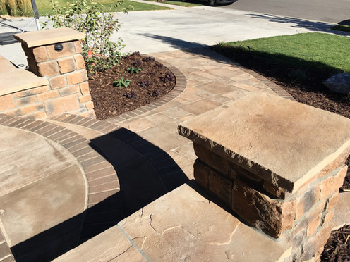 Buff sandstone top caps, Ashlar cut pavers and curving stone edge banding gives grace to exensive hardscape.  Banding continues along the path for a more formal feel.  Lighting is an important part of design creating ambience after dark.