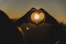 hands-making-shape-heart-with-sun-middle