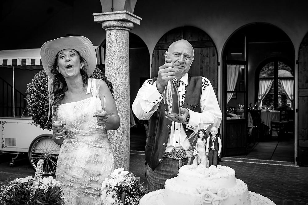 Taglio della torta e spumante sposi fotografia bianco nero
