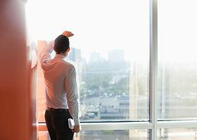 L'homme regardant à travers une fenêtre
