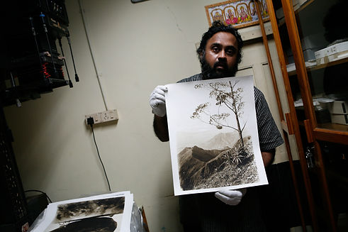 A man from South India holds up a historic sepia-toned landscape photograph.