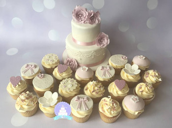 Pink and white wedding cake and cupcakes