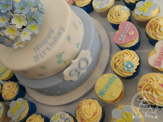 Pretty 90th birthday cake with handmade flowers and cupcakes