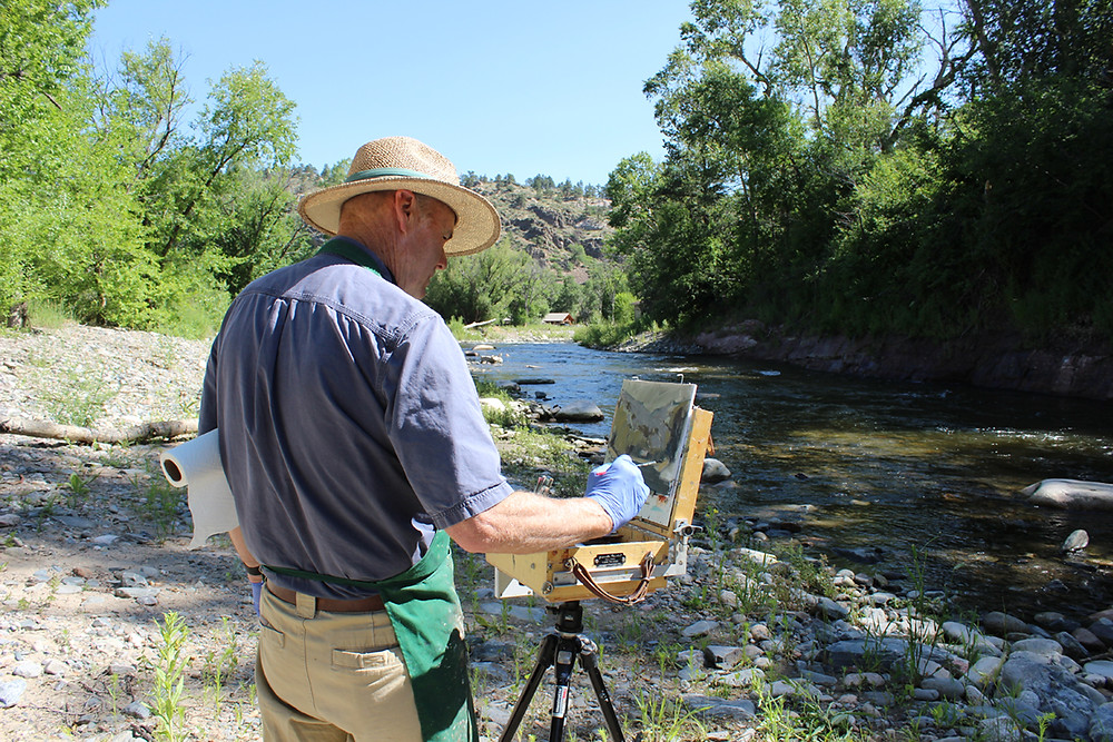 George Coll painting at the Big Thompson river at Sylvan Dale Ranch during one of his classes.