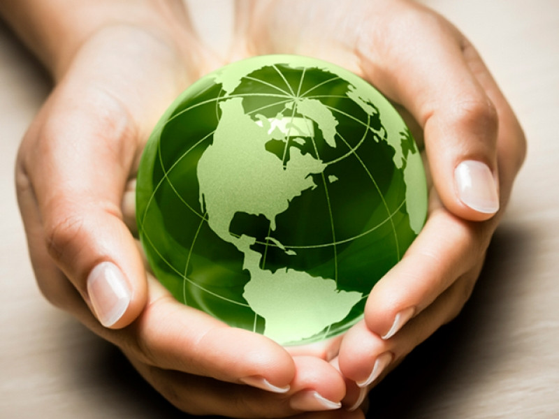 A green planet Earth in the outstretched palms of a pair of hands