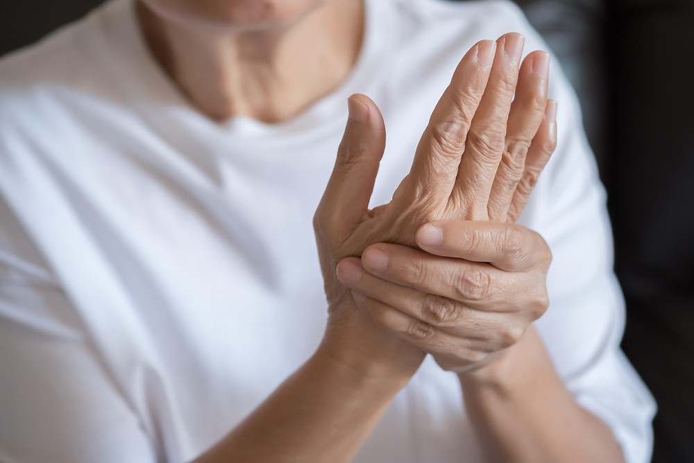 A person gripping their painful arthritic hands