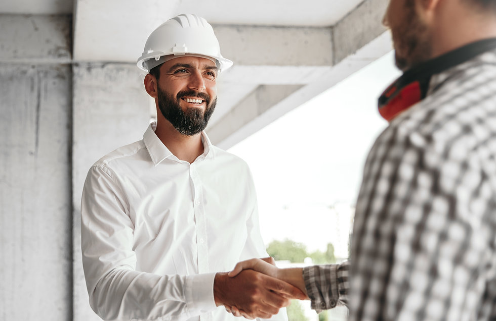 Bearded man in helmet smiling and shaking hand of crop coworker during work on constructio
