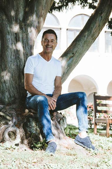Franz Hirschmann sitzt auf einem Baumstamm und lächelt