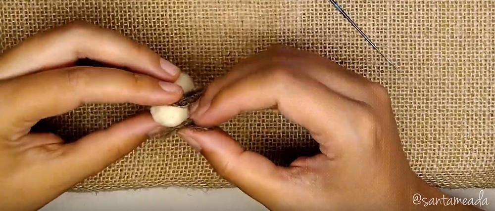 mini coelhinho de lã com feltragem com agulha colocando as orelhas