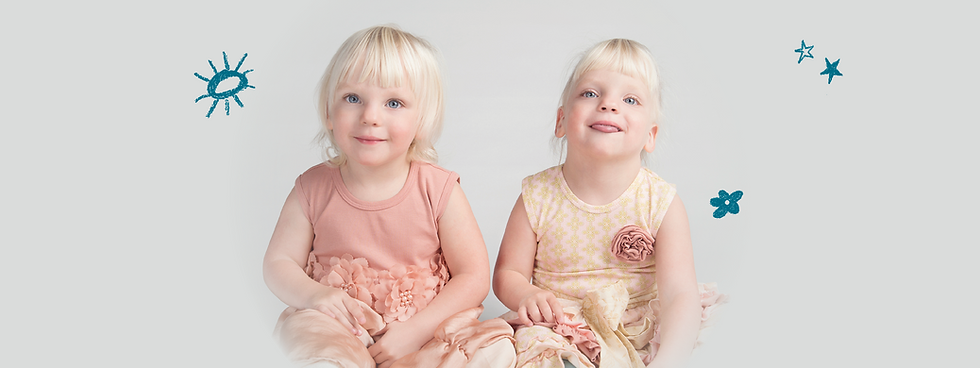 Twin blonde girls with special needs sitting and smiling at the camera