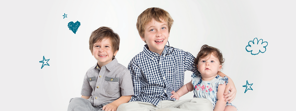 Three siblings sitting together smiling. There are two young brothers and one baby sister