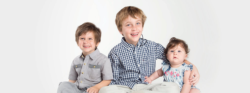 Photo of 3 siblings of varying ages, 2 brothers and one baby sister