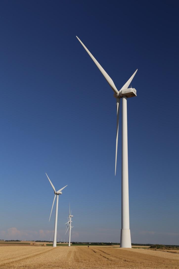 Eolienne décentrée au 1er plan à droite, dans un champ, il y a d'autres éoliennes dans le fond, en bas à gauche en petit