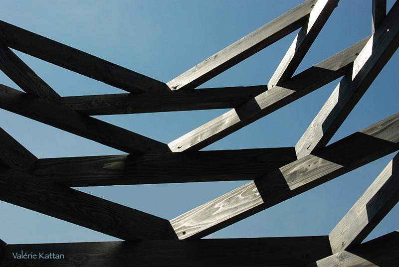 Défi photo voir les formes, photo abstraite montrant une structure en bois formant des triangles, l'arrière plan étant le ciel