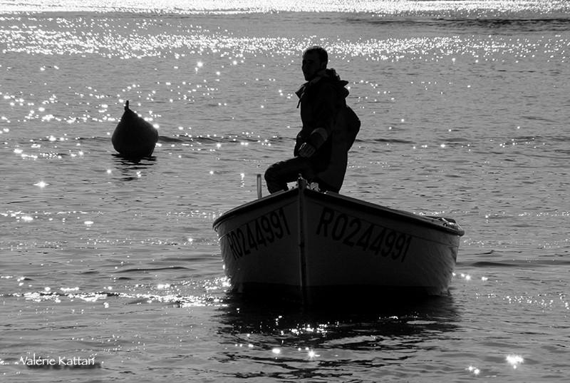 barque sur la seine en contrejour, un homme est debout pour piloter