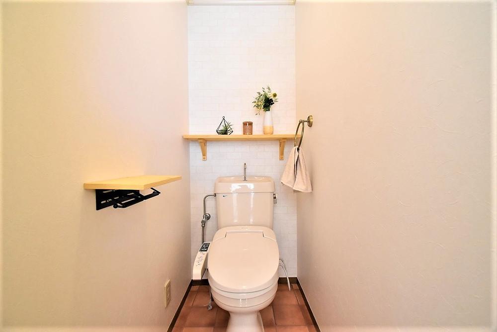 両側の壁紙は、消臭効果が期待できる特殊なクロスを施工。床は、テラコッタ風のクッションフロアを採用して、おしゃれ感を演出。また棚を新たに取り付けて植物などを置くと、おしゃれなトイレになります。