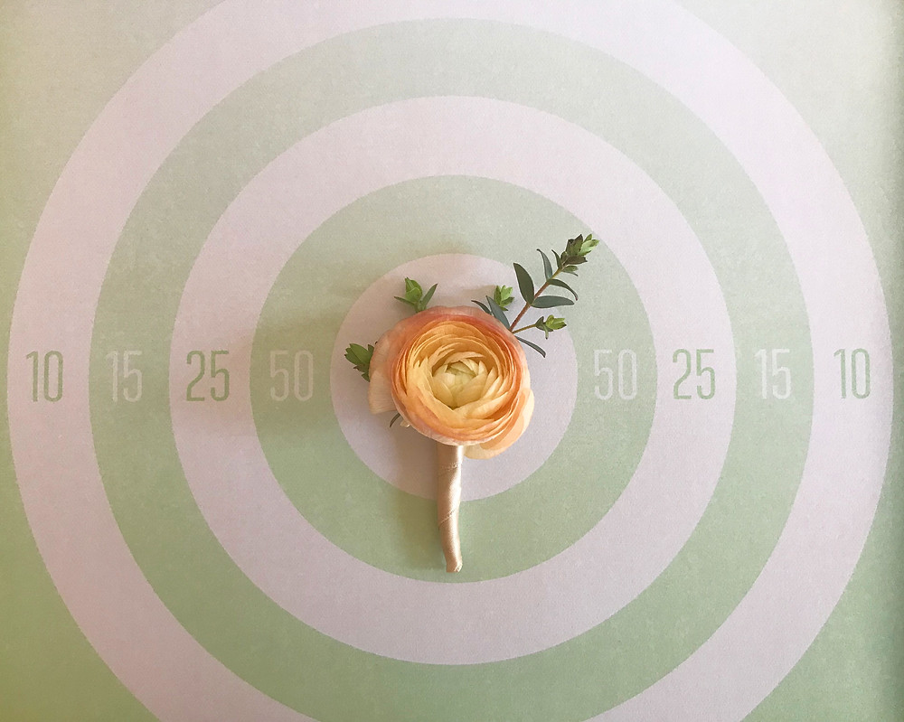 Peach ranunculus boutonniere wrapped in champagne ribbon with gunning eucalyptus