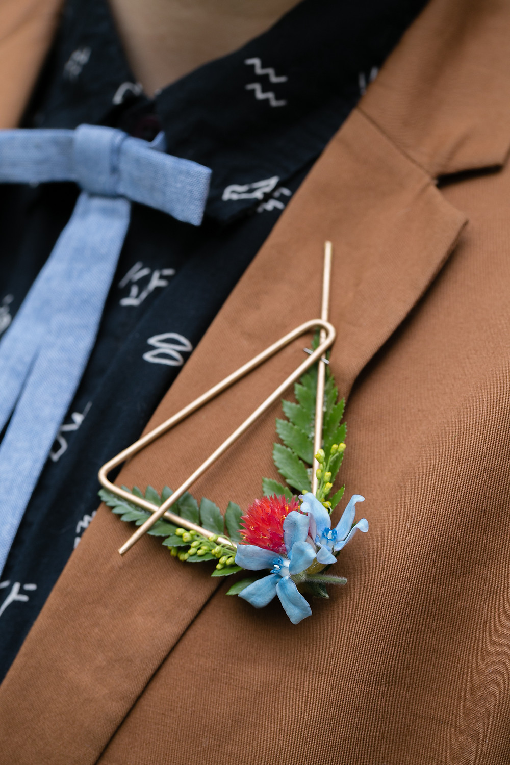 Gold metallic groom's boutonniere with primary color flower accents