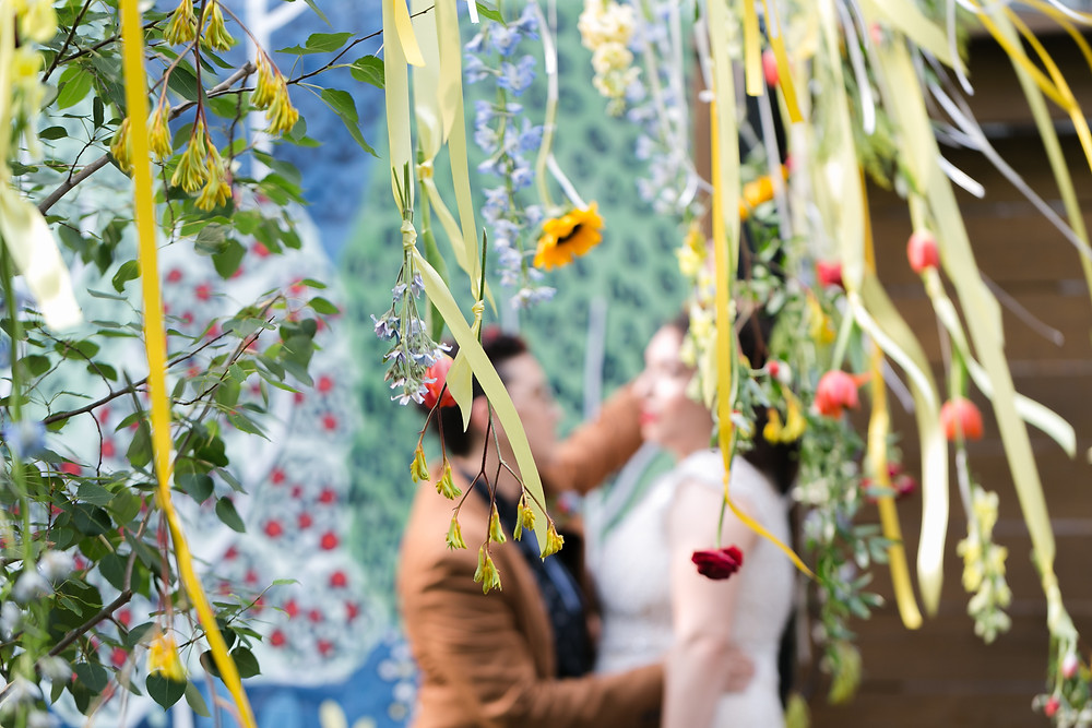 Hanging flowers with yellow ribbon at a wedding in an urban garden