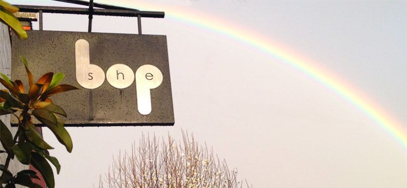 Photograph of a sign reading She Bop and hanging in front of a sky with a rainbow
