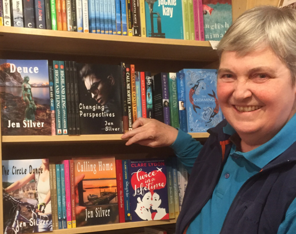 woman stands in front of a bookstore shelf smiling