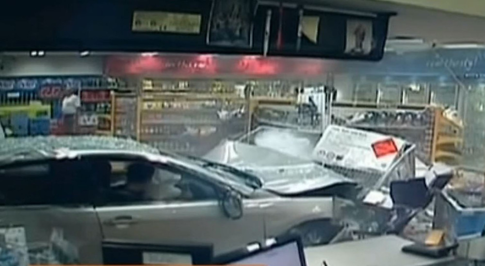 Image of a vehicle crashed into a petrol station store. A damaged gas cage is visible in front of the car.