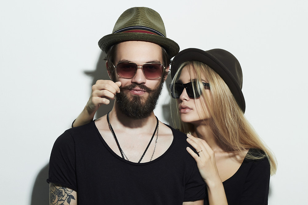 Man with hat and beard Woman with hat touches beard