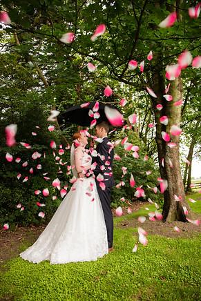Bride and groom with umbrella and confetti