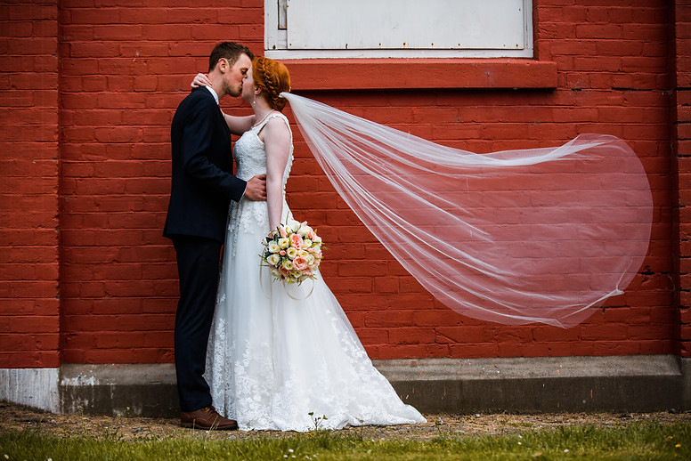 Bride and groom standing next to red brick wall