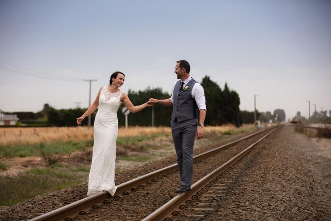 Bride and groom walking on railway
