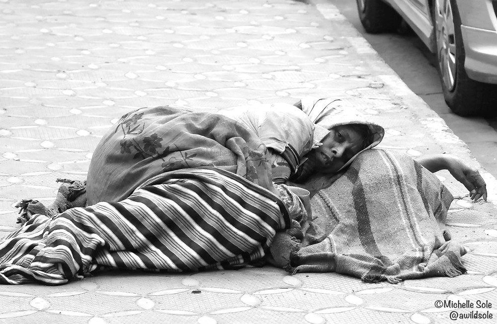 A beggar wrapped in blankets n black on white on the streets of Calcutta, India