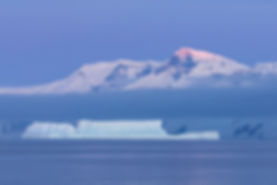 Iceberg and snow capped mountains across the ocean at sunset in Antarctica