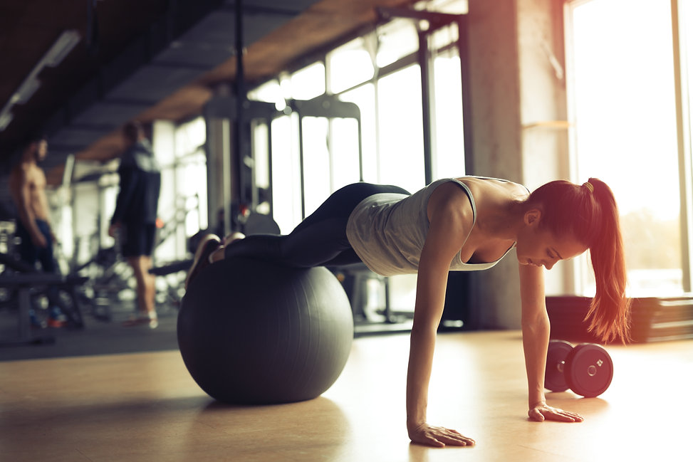 Beautiful woman training pilates in gym.