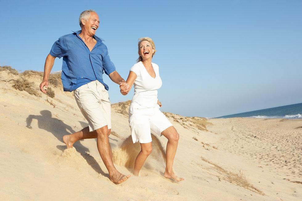 Senior Couple Enjoying Beach Holiday Running Down Dune.jpg