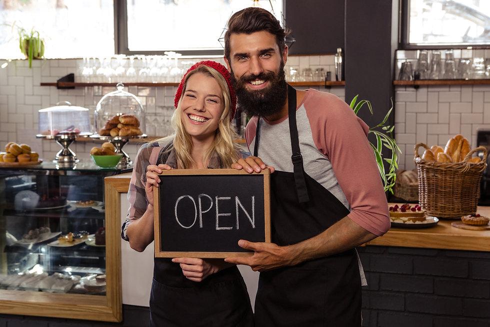 Waiter holding blackboard with open in t