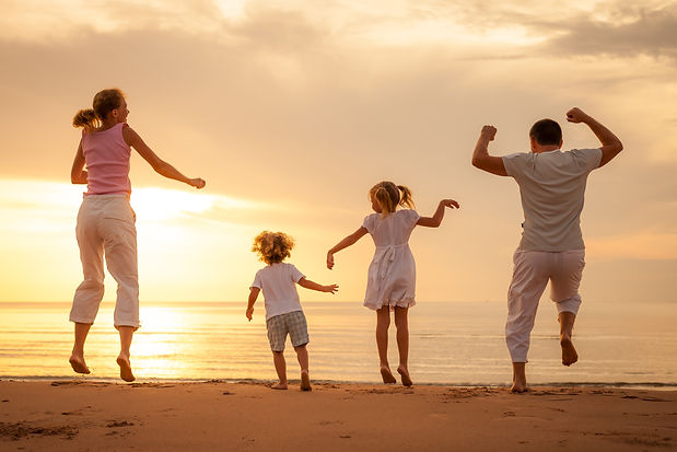 Happy beautiful family dancing on the  beach on the  dawn time..jpg