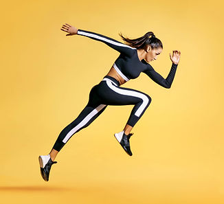 Sporty woman runner in silhouette on yel