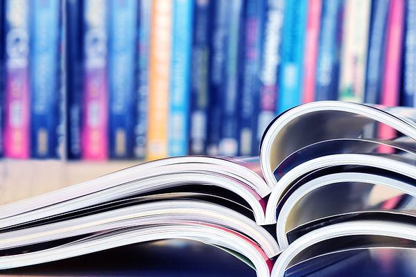 close up stacking of opened magazine wit