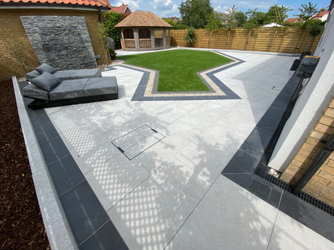 This outdoor living space was created by Jasper and his team using The Patio Supply Centre Arb Blanco for the main patio with a Gam Noir Border porcelain tiles and Storm Natural Stone Wall Cladding for the water feature.