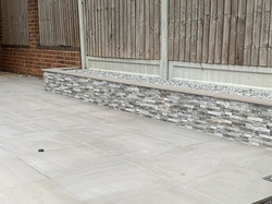 Grey porcelain tile Taupe, together with raised bed edging in Natural stone cladding.