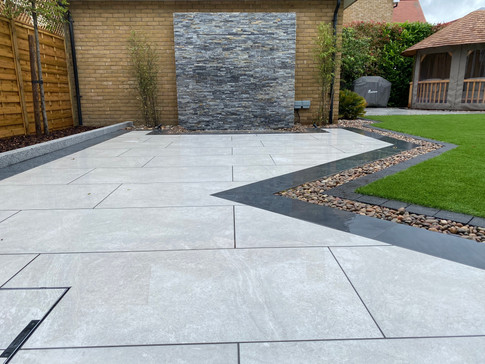 This outdoor living space was created by Jasper and his team using The Patio Supply Centre Arb Blanco porcelain tiles with a Gam Noir border and Storm Natural Stone Wall Cladding for the water feature.