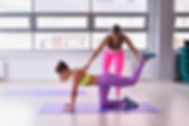 Personal trainer helping girl in stretch