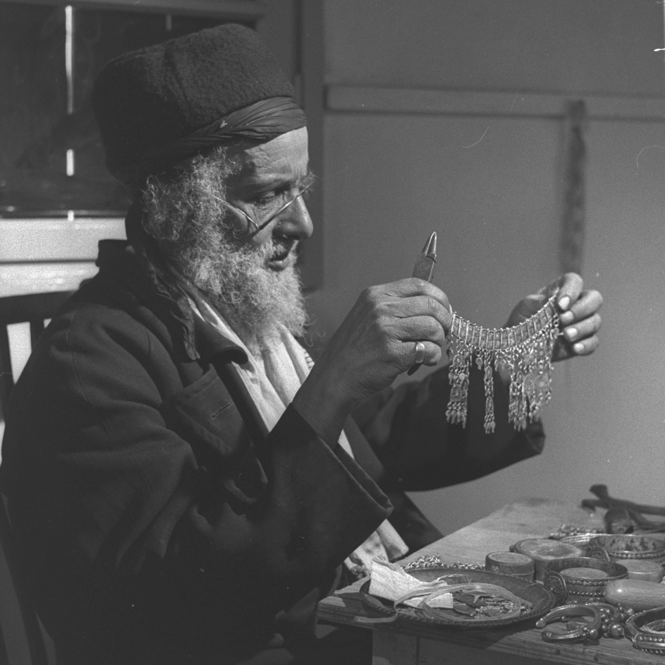 """65 YEAR OLD YOSES YOSEF, A SILVERSMITH FROM YEMEN, FOLLOWS HIS TRADE HERE, FILLING ORDERS BY """"MASKIT"""" YOSEF CAME HER 8 YEARS AGAIN ON THE """"MAGIC CARPET""""."""