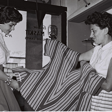 MRS. RUTH DAYAN SHOWING A HAND-MADE ORIENTAL-STYLEBLOUSE TO NEWLY ELECTED ISRAEL'S BEAUTY QUEEN SARAH TAL AT THE MASKIT SHOP ON BEN YEHUDA STREET IN TEL-AVIV.