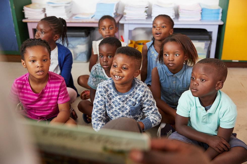 Teacher reading book to elementary school children in class.jpg