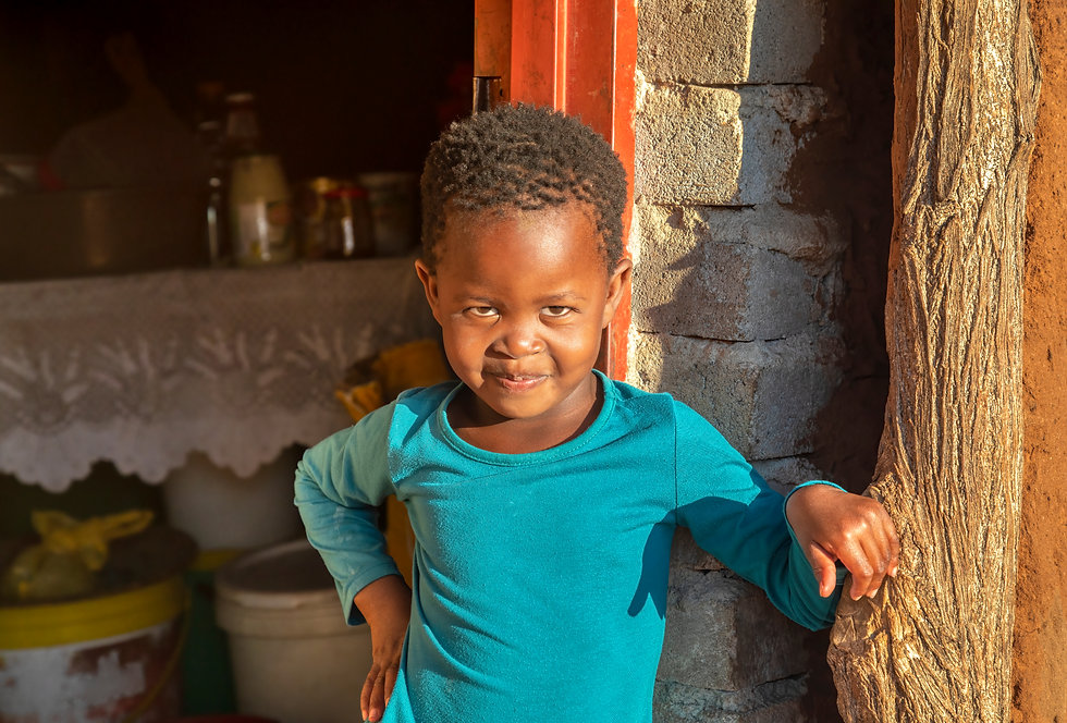 African village, child standing in front of the house in a sunny day.jpg