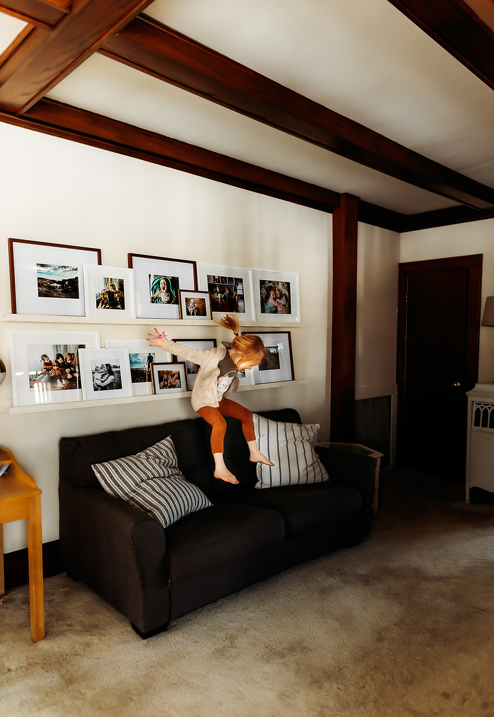 Little girl jumping on couch in front of gallery wall display