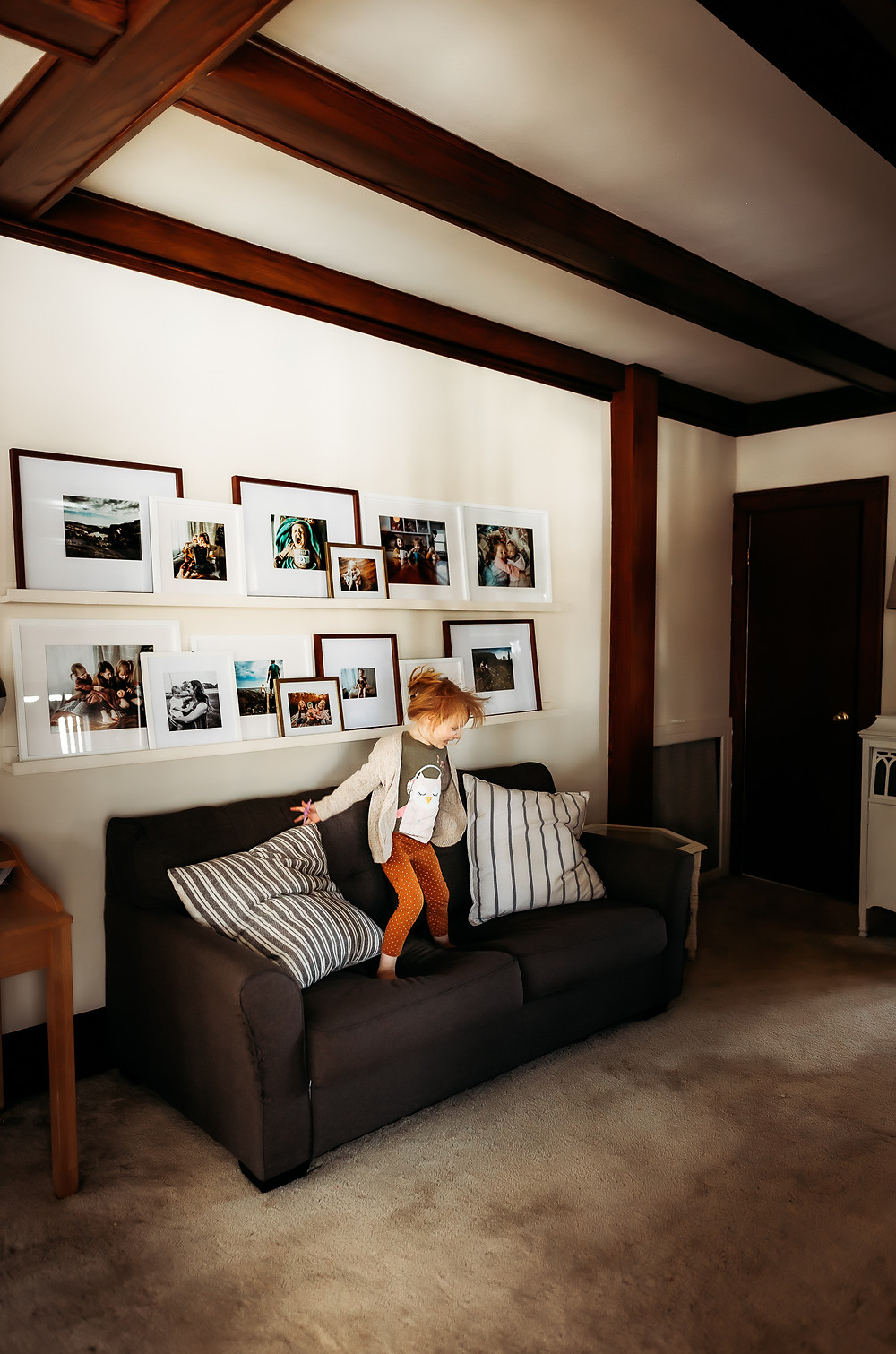 Owatonna family photographer, little girl jumping on couch with gallery wall of photos behind her