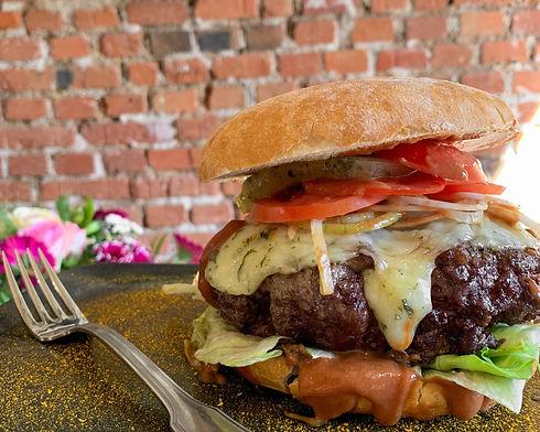 Burger du restaurant le Théâtre à Colmar avec un steak de boeuf de 300g, des tomates, cornichons, fromage ribeaupierre et oignons. Burger XXL avec sauce du Théâtre.